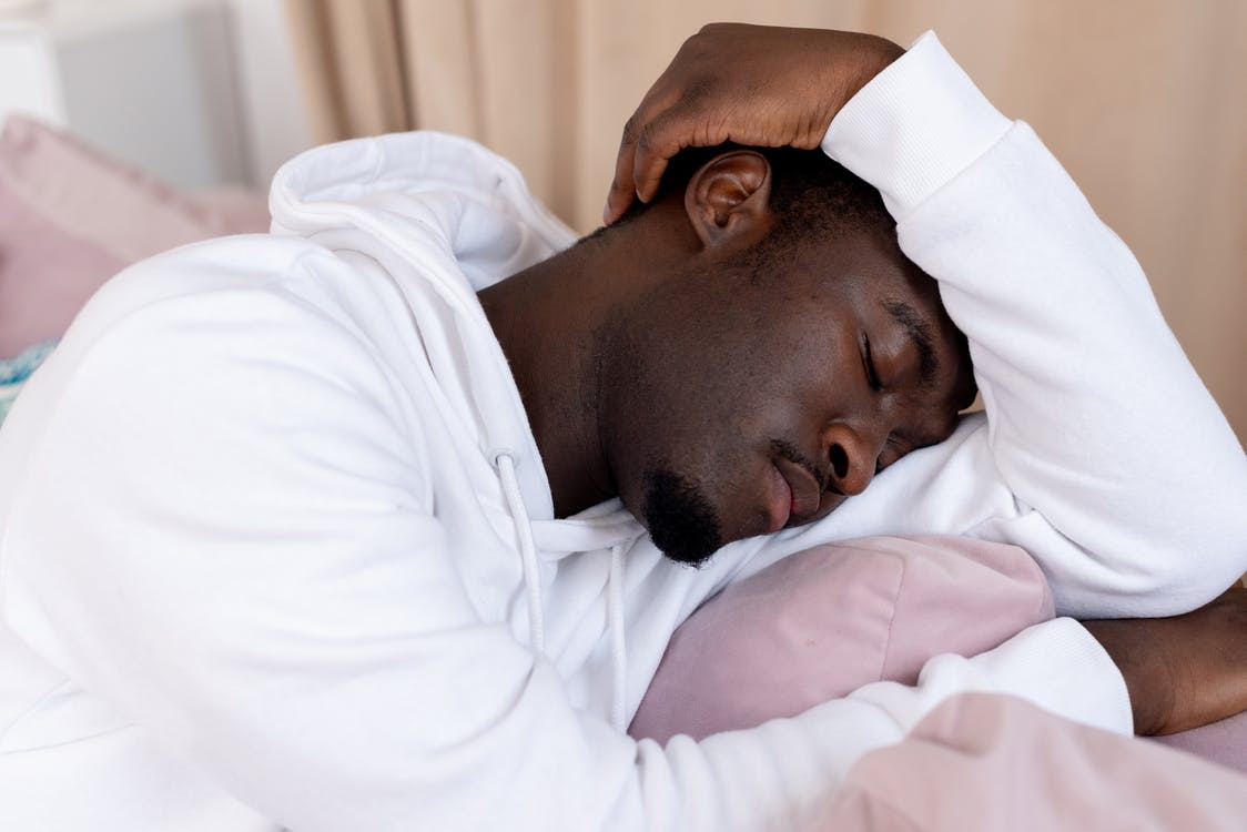 African American male with short dark hair in white hoodie leaning on hand and sleeping in light room