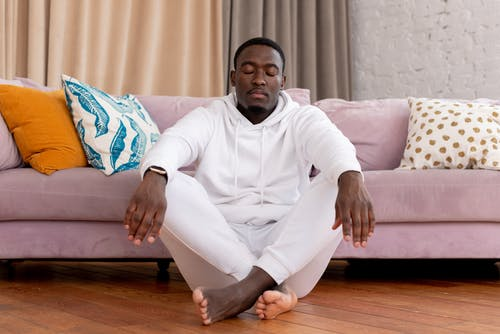 Calm African American male in white clothes sitting with closed eyes and crossed legs on floor against comfortable sofa in living room