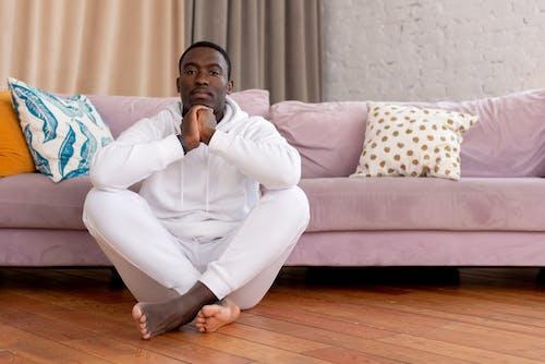 Black man sitting on floor in living room
