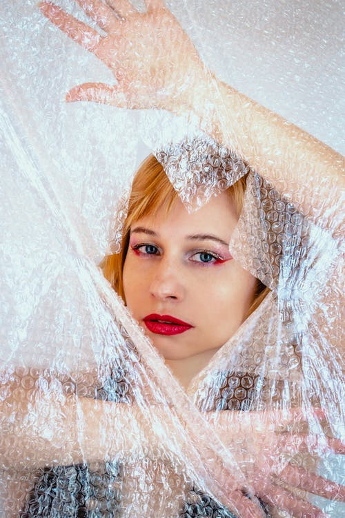 Millennial woman with makeup and brown hair peeking out of bubble pack hole while looking at camera
