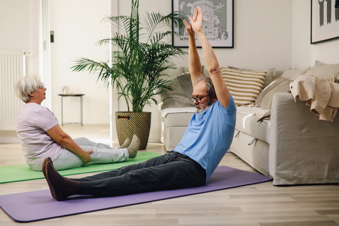 Man in Blue Tank Top and Blue Shorts Lying on Blue Yoga Mat