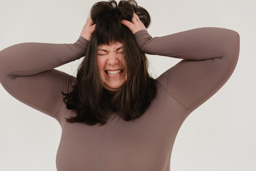 Young obese woman rumpling hair with closed eyes in white studio