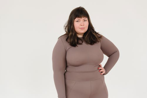 Plus size female in activewear keeping hand on waist and looking at camera against white background