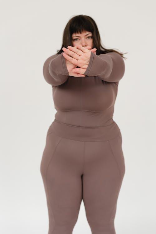 Overweight woman showing stop gesture in studio