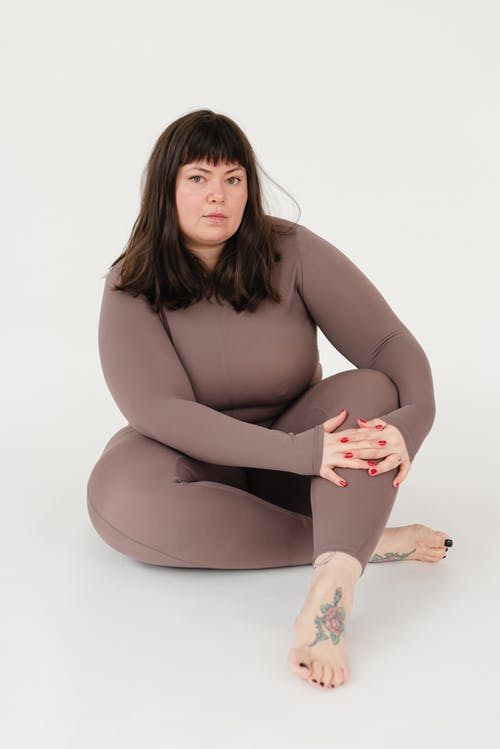 Full body of serious overweight female in sportswear embracing knee while sitting with legs crossed against white background and looking at camera