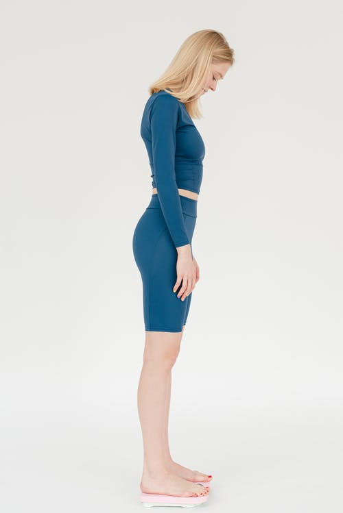 Full body side view of slender female in sportswear checking weight on scales and looking at result against white background