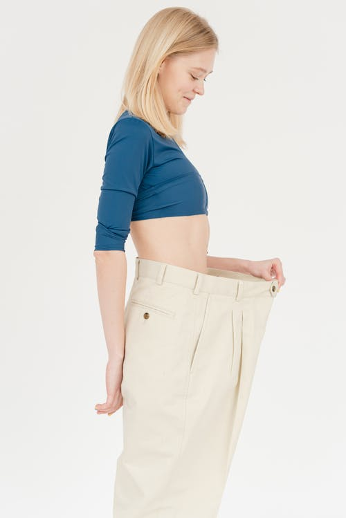 Side view of slim positive female with bare belly wearing oversized trousers standing on white background in light studio after weight loss