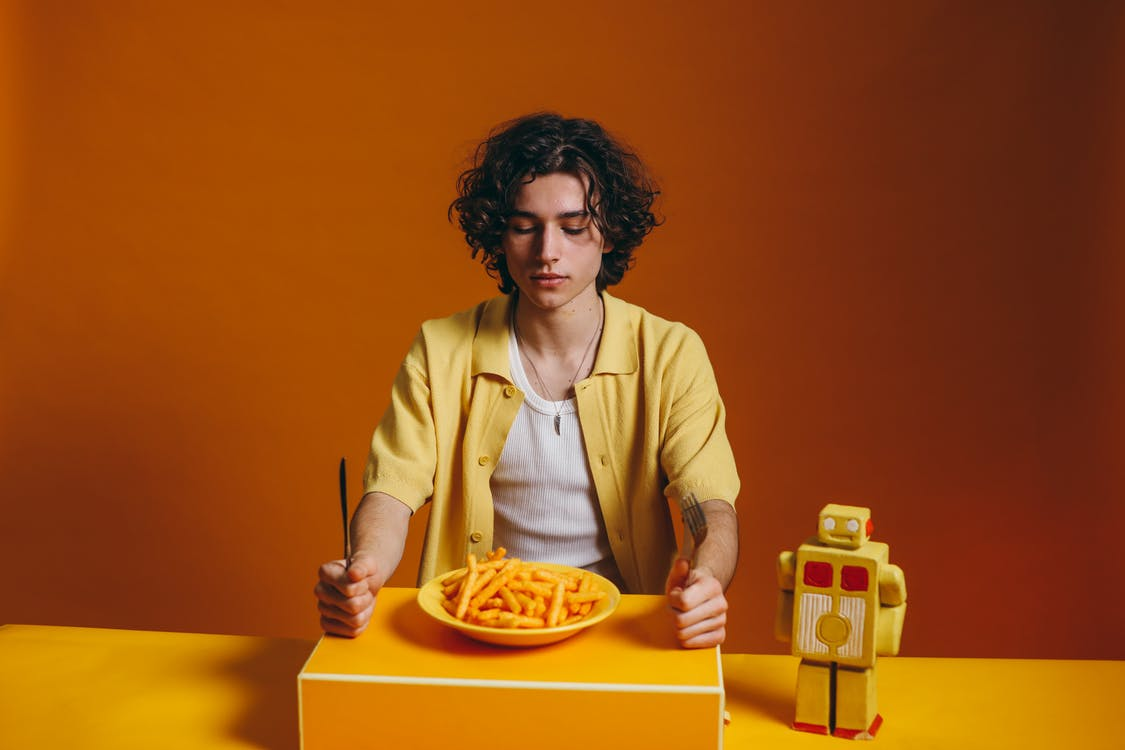 Young Man Looking Down On A Plate Of Fries