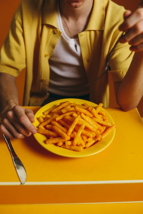 Crop Photo Of Man Eating A Bowl Of Fries