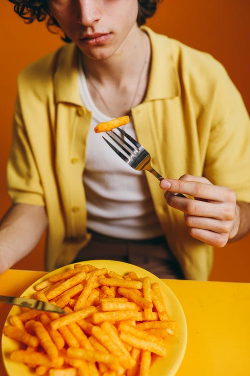 Crop Photo Of A Young Man Eating French Fries