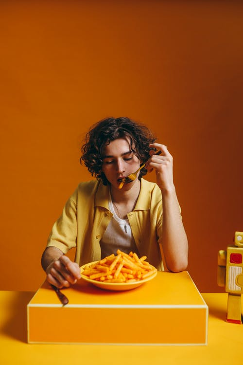 A Young Man Eating French Fries