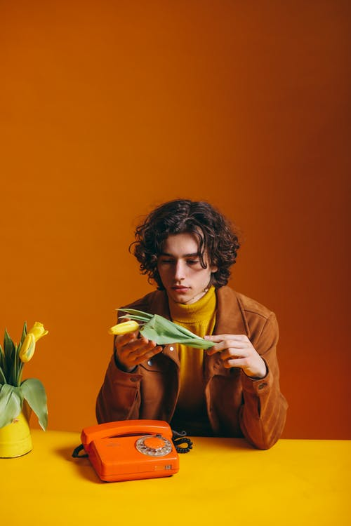 Man in Brown Coat Holding Yellow Flower