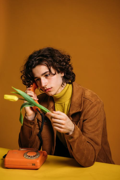 Guy In Brown Coat Holding A Yellow Flower