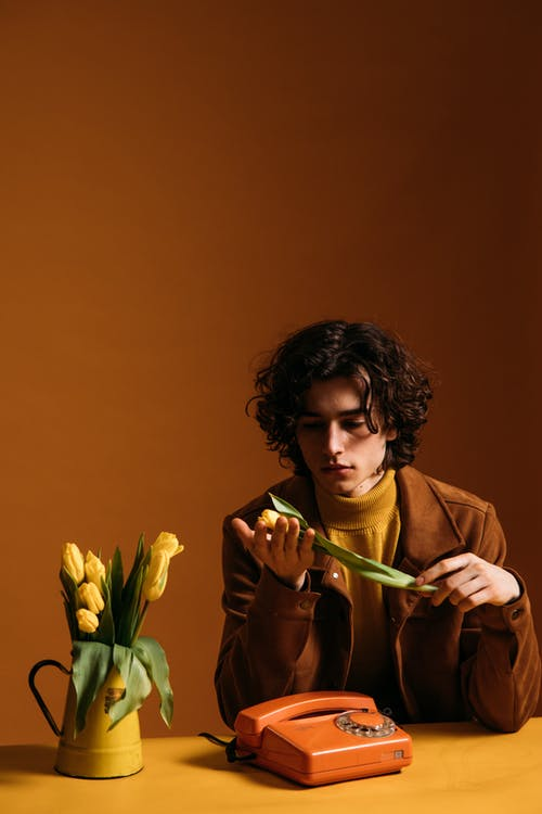 Young Man in Brown Coat Holding Yellow Tulips
