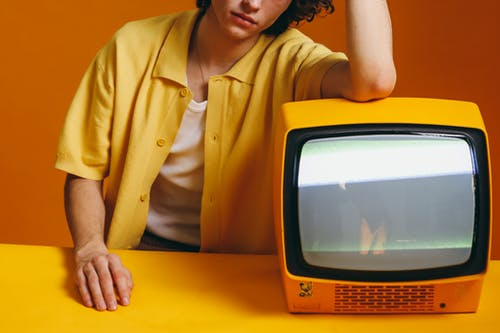 Crop Photo Of Young Man Sitting Beside A Yellow TV