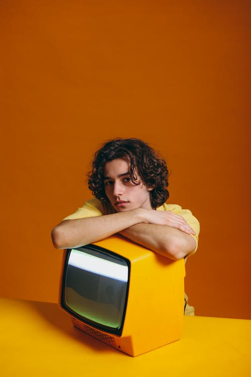 Young Man Sitting Beside A Yellow Television