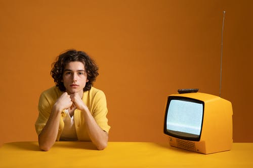 Young Man Sitting Beside A Yellow TV