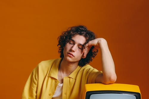 Young Man Sleeping Beside A Yellow Tv