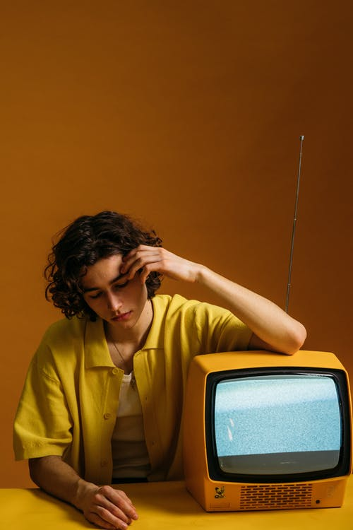 A Guy Sitting Beside A Yellow TV With Blank Screen