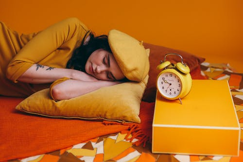 Woman Lying on Bed Beside A Yellow Analog Alarm Clock