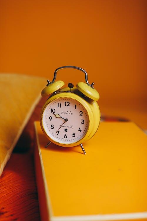 Yellow Alarm Clock On Yellow Surface