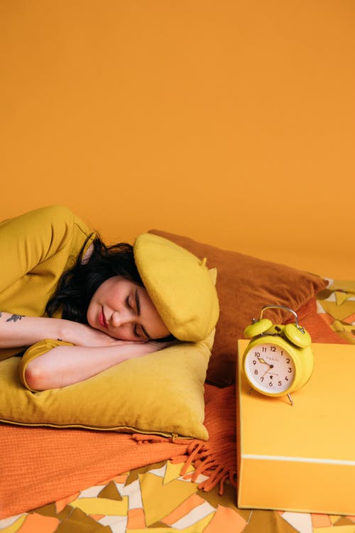Woman Lying on Bed With Yellow Pillow