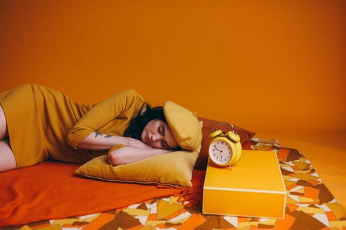 Photo Of Woman In Yellow Outfit Lying Down Beside An Alarm Clock