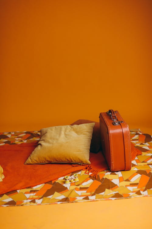 Brown Leather Bag Beside Brown Pillow