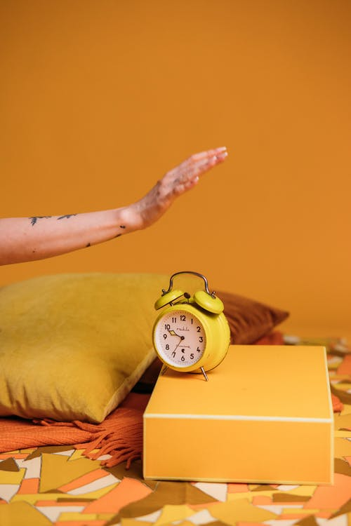 Yellow Alarm Clock On A Yellow Box