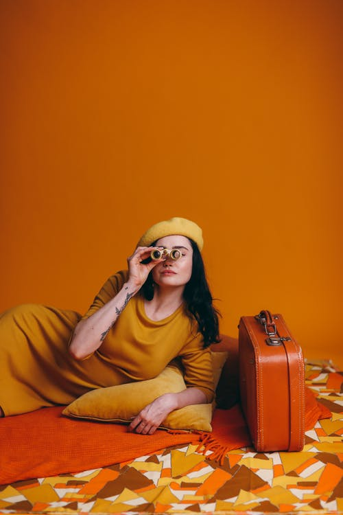 Woman In Yellow Outfit Holding A Yellow Binoculars