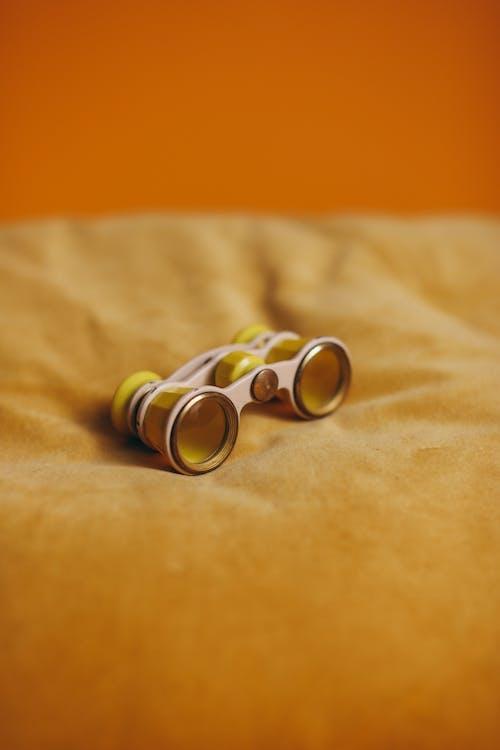 Yellow And Silver Binoculars on Yellow Textile