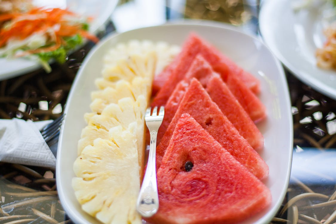 Sliced Watermelon and Pineapple Fruit With Stainless Steel Fork Placed on White Ceramic Rectangular Plate