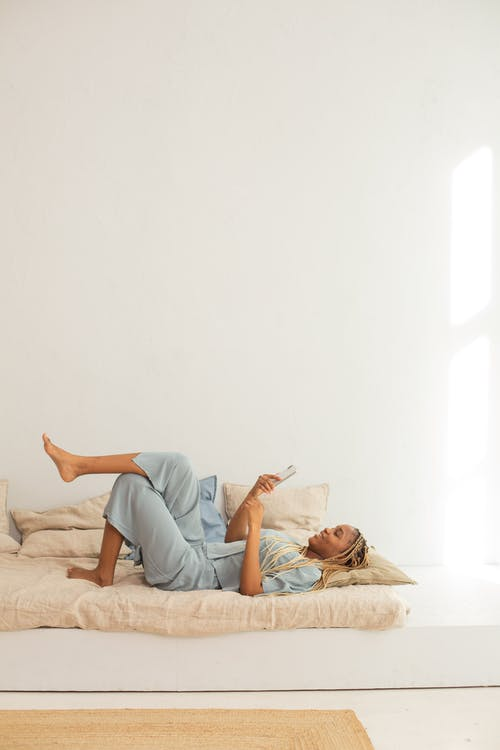 Woman in Blue Pajamas Lying on Bed while Using her Phone
