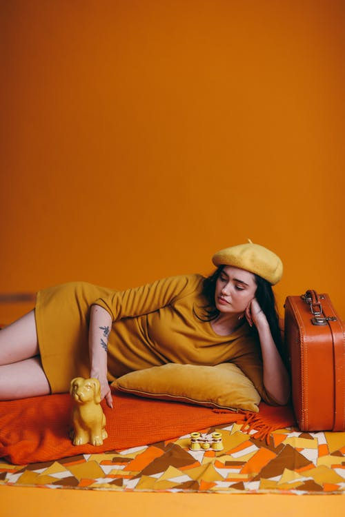 Woman in Yellow Long Sleeve Shirt and Brown Pants Lying on an Orange Color Textile
