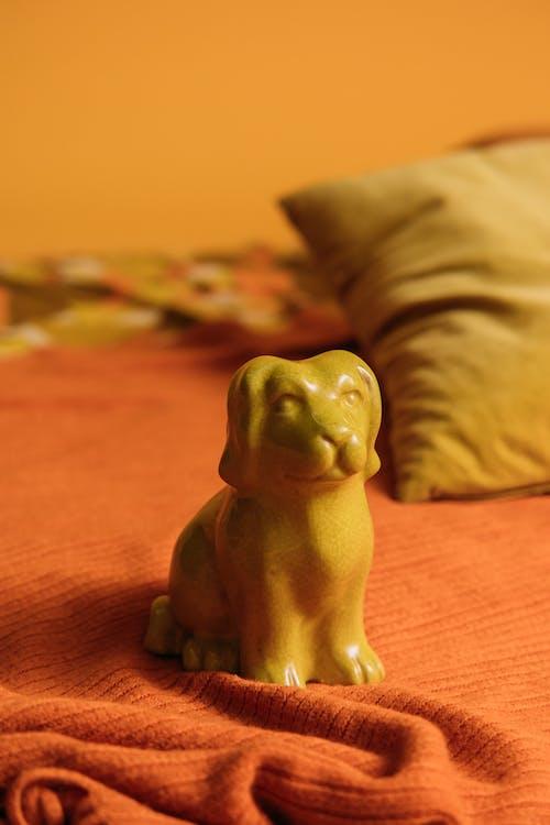 Yellow Dog Figurine on Bed