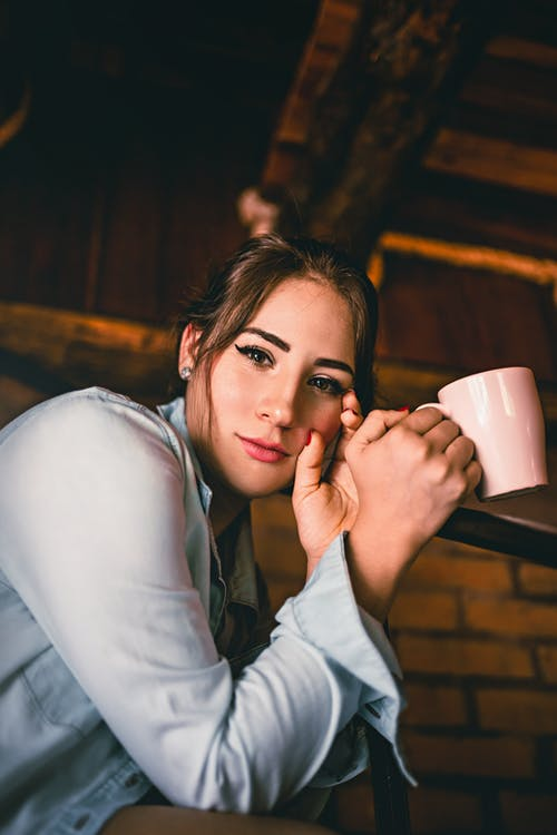 Young female with mug of hot aromatic coffee looking at camera on blurred background