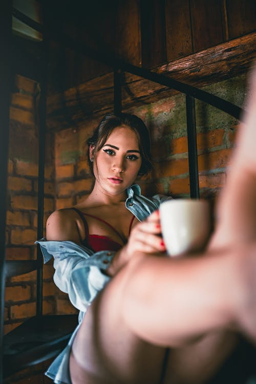 Sensual young woman in red bra and shirt with cup