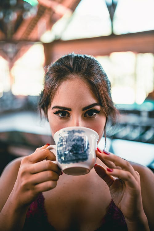 Content young female drinking tasty organic mug of coffee on blurred background in daytime