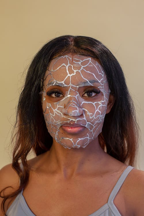 Young calm ethnic female in casual top wearing hydrating facial cloth mask and looking at camera