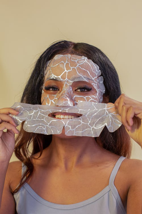 Smiling attractive ethnic female in casual top removing hydrating facial cotton mask and looking at camera against beige wall