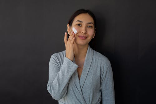 Positive ethnic female in bathrobe applying moisturizing cream on cheek during daily beauty routine against black background and looking at camera