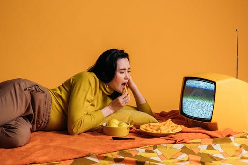 Woman in Yellow Long Sleeve Shirt Watching TV And Eatinghi