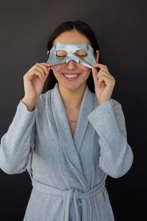 Smiling woman taking off sheet mask