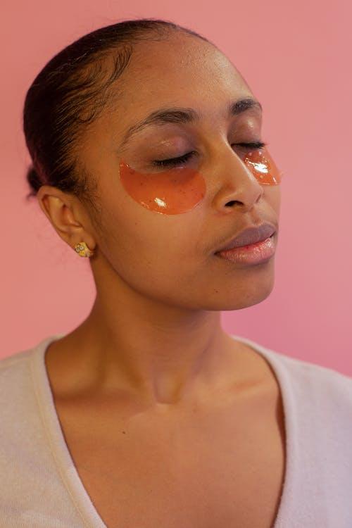 Serene black woman in gel eye patches in studio