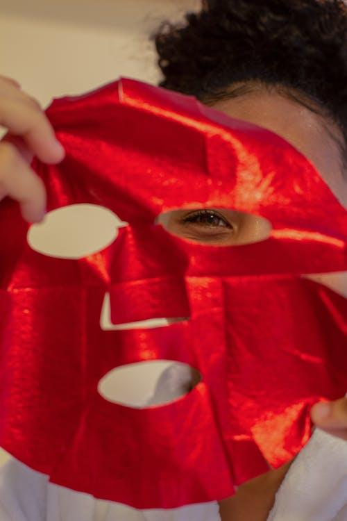 Black woman applying bright sheet mask