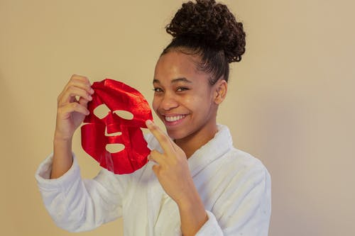 Cheerful black teenager with hydrating mask on beige background