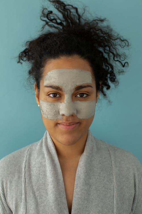 Black woman with cleansing mask on face