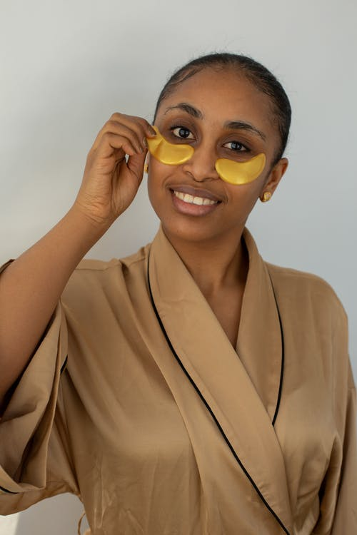 Young smiling African American female in robe removing hydrogel eye patch from face while looking at camera