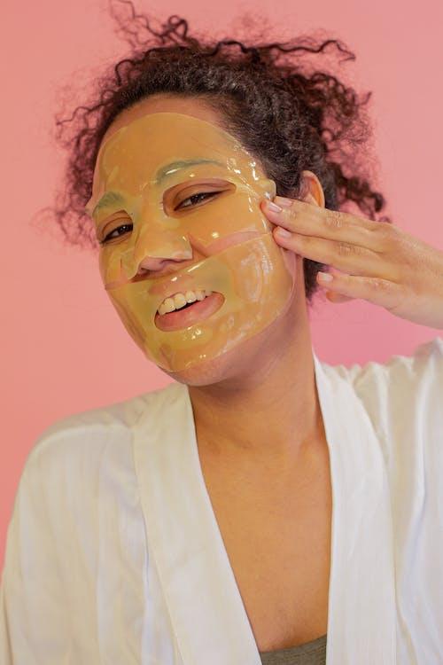 Cheerful ethnic woman applying rejuvenating mask sheet on face