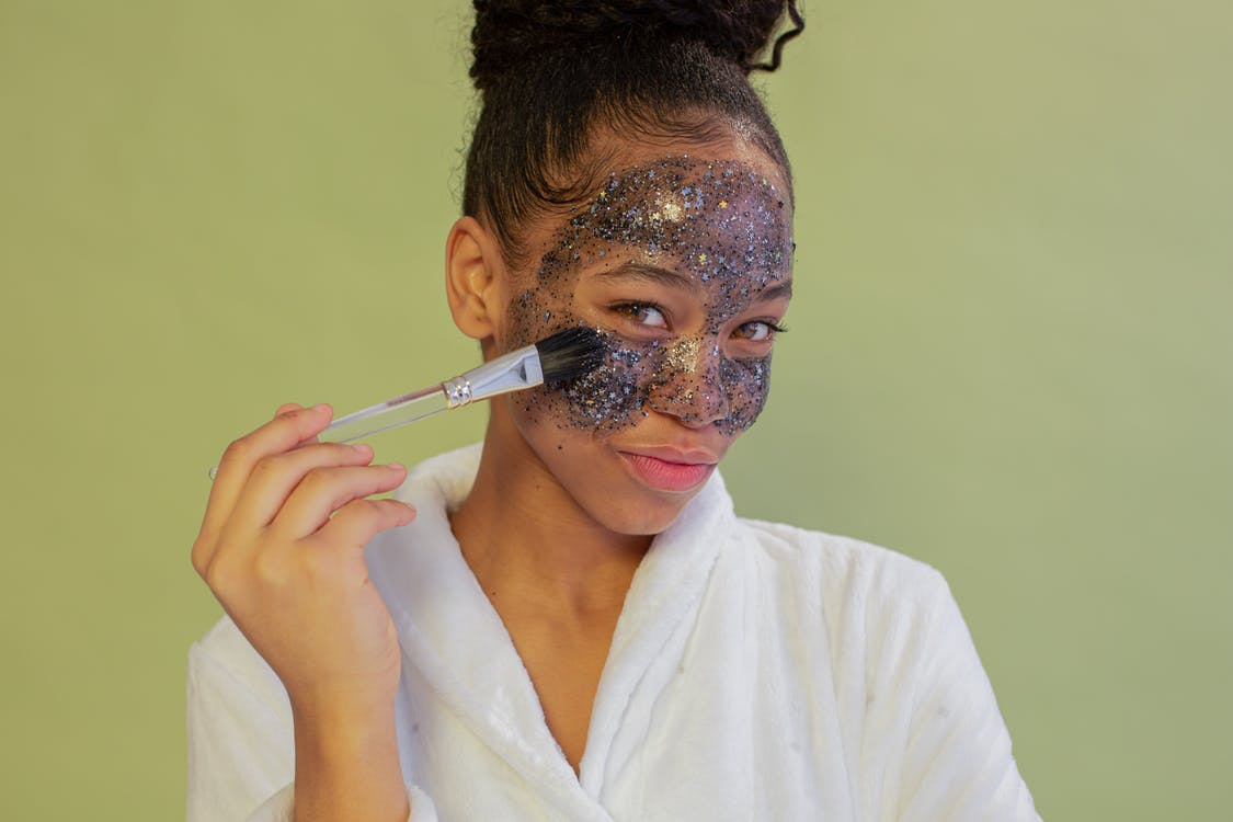 Positive black woman applying sparkling face mask with brush